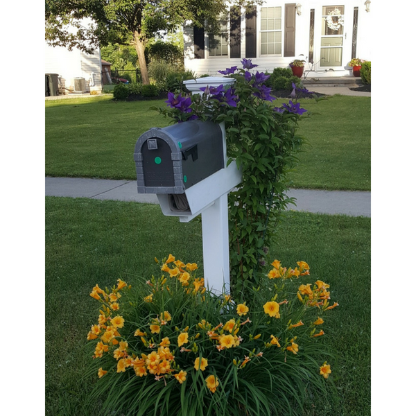 A Mailbox Post planted at the back and with flowers planted around the base