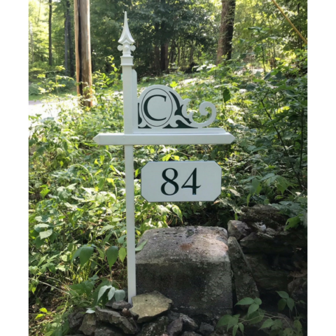 A white lawn sign holder with a customized house number and monogrammed corner