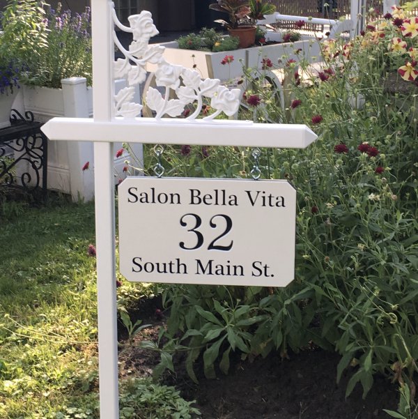 Custom black and white engraved sign made for a local salon on one of our white lawn sign holders with rose scroll