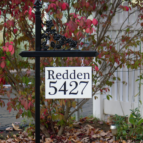 Custom black and white engraved sign with family name and house number on one of our black lawn sign holders
