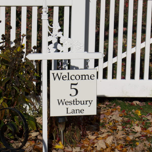 Custom black and white engraved welcome sign on one of our white lawn sign holders with a rose scroll