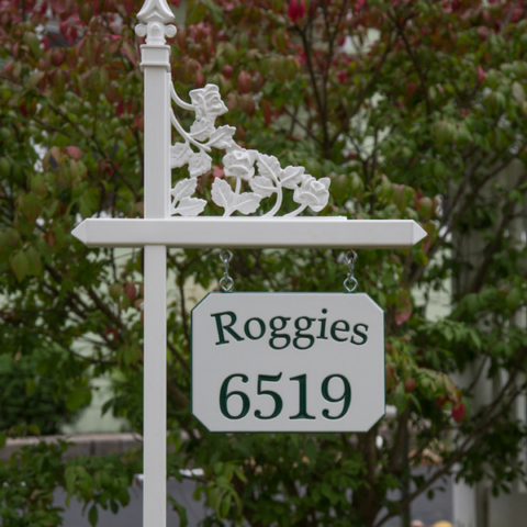 Custom green and white engraved sign with family name and house number on one of our white lawn sign holders with rose scroll