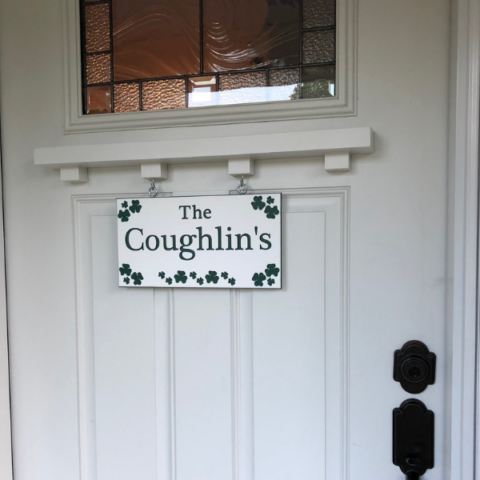 Custom green and white engraved sign with family name and shamrock design