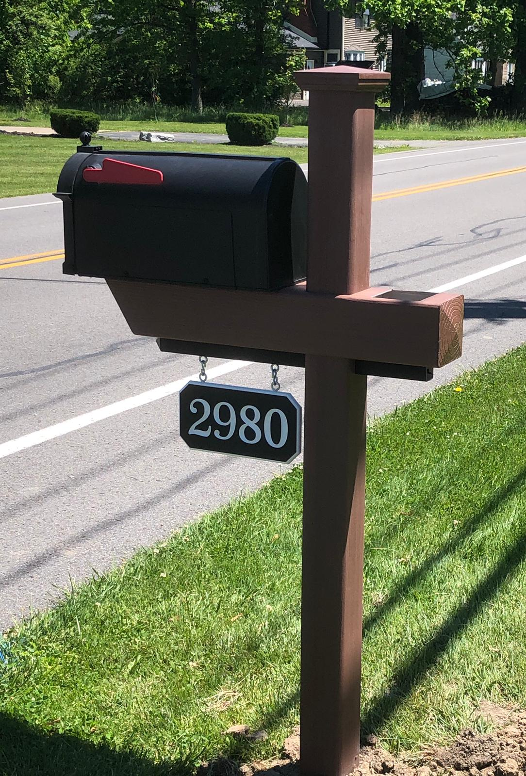 Essential Woodgrain Mailbox Post in Brazilian Blend with custom black-white-black engraved house number sign.