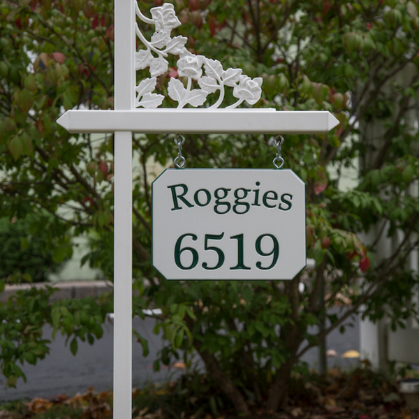 White lawn sign holder with a customized sign showing a special family name with a slight arch on white-green-white color core